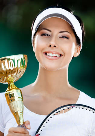 Tennis player won the cup at the sport contest. Victory photo