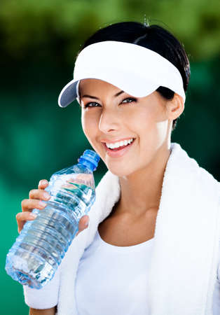 Sporty woman with plastic bottle of water after tennis training Stock Photo - 15868021
