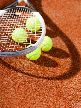 Close up view of tennis racquet and balls on the clay tennis court photo