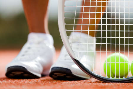 Legs of sportive girl near the tennis racquet and balls Stock Photo - 15873472