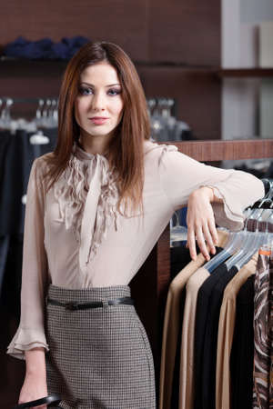 Beautiful woman in the shop with wide choice of clothes photo