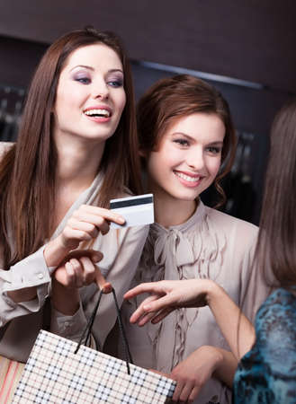 Pretty women settles an account with credit card at the store photo