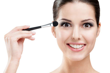 Woman applying make up with brush, isolated on white. Beauty procedures photo