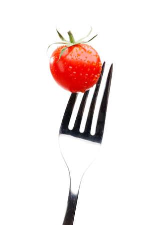 Cierre de tomate rojo en el tenedor, aislado en blanco. Alimento dieta saludable