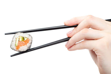 Hand holding fresh maki sushi roll with black chopsticks, isolated on white