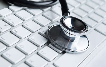 solucion de problemas: Primer plano de estetoscopio en el teclado del PC. Concepto de salud Foto de archivo