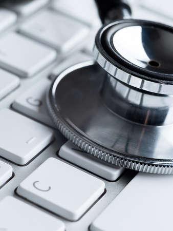 solucion de problemas: Primer plano de estetoscopio en el teclado del ordenador. Medicina concepto
