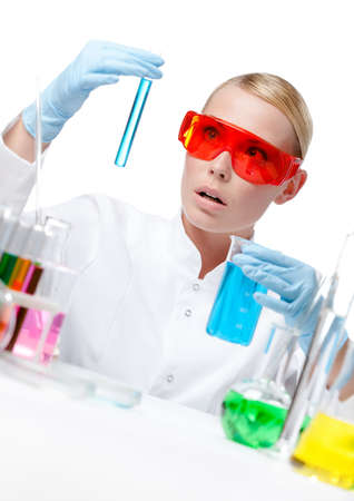 Amazed female doctor in spectacles does some experiments, isolated on white Stock Photo - 15929124