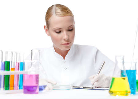 Lab assistant surrounded by medical glassware makes some notes, isolated on white photo