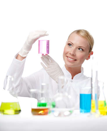 Young lady scientist looks at the beaker full of purple liquid, isolated on white photo