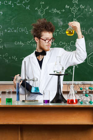 pry: Mad professor examines Bunsen flask with yellow water after the experiment in his laboratory