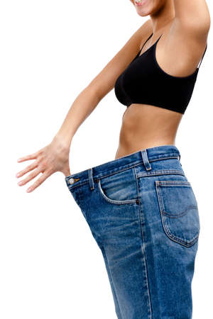ideal: Body of a slim girl wearing huge jeans, isolated on white