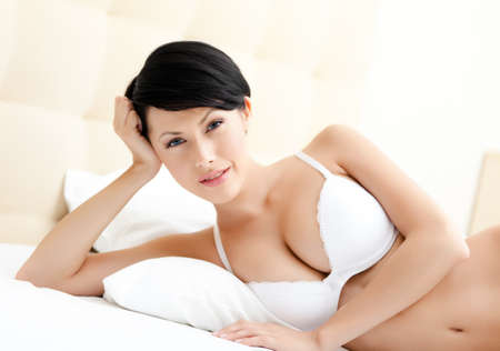 lying on side: Woman in underwear is lying in the wonderful bed Stock Photo