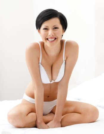 gladly: mujer se sienta sobre la cama, fondo blanco Foto de archivo