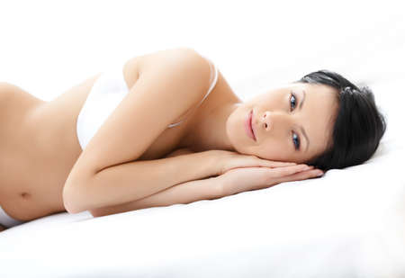Woman in underwear is lying in the comfortable bed, isolated on white photo