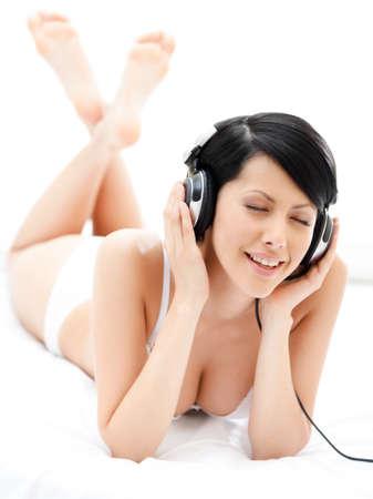 sexualidad: Mujer en sujetador escucha música a través de los auriculares negros, fondo blanco Foto de archivo