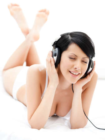 top: Woman in bra listens to music through the black earphones, white background