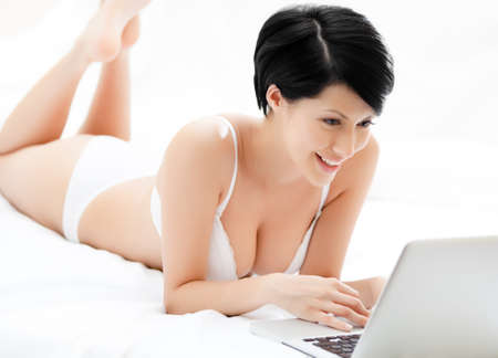 woman bra: Woman in underwear is working on the computer while lying on the bed, isolated on white background