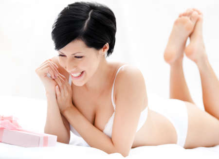 Woman in underwear finds a surprise in bed, white background Stock Photo - 15928684