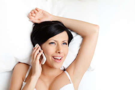 Woman in underwear speaks on mobile phone while lying in the bed, white background photo