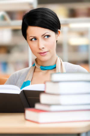 interested: Woman surrounded with piles of books reads sitting at the table at the reading hall. Learning process Stock Photo