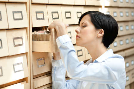Woman searches something in card catalog composed of set of wood boxes at the library. Study photo