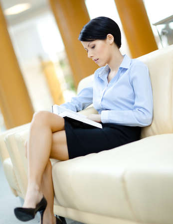leather skirt: Businesswoman rests at the sofa reading book at the hall