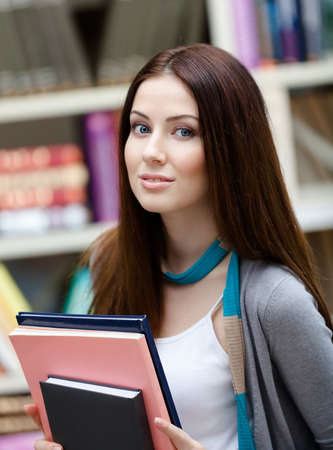 Female student with books at the library. Research. Study photo