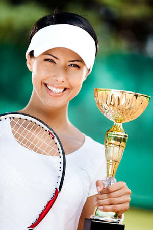 Successful tennis player won the cup at the sport competition. Victory photo