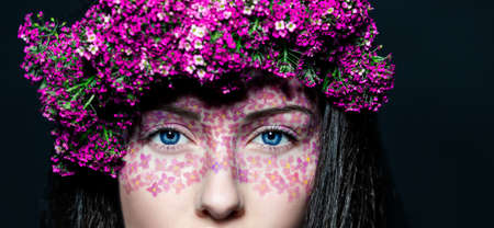 Portrait of young beautiful fresh girl with creative make-up and pink flowers photo