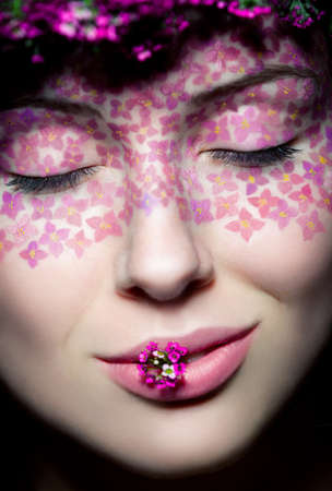 Close up view portrait of model with flowered wreath and fashion make up with eyes shut photo