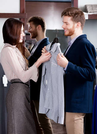 haute couture: Young man consults with girlfriend while selecting a shirt Stock Photo
