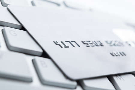 buy one: Close up of credit card on a pc keyboard. Concept of internet buying