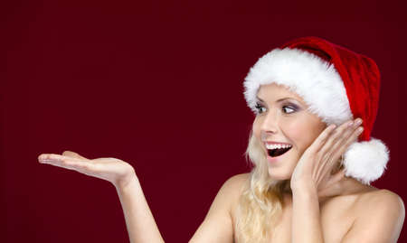 mas: Pretty woman in Christmas cap gestures palm up, isolated on purple Stock Photo