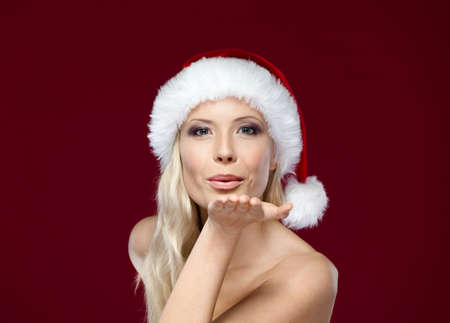 x mas: Beautiful woman in Christmas cap blows kiss, isolated on purple Stock Photo