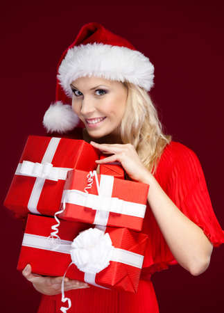 Pretty lady in Christmas cap holds a set of presents wrapped with red paper, isolated on purple photo