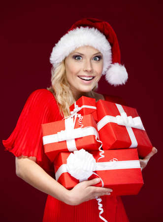 Young woman in Christmas cap holds a set of gifts wrapped with red paper, isolated on purple photo