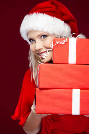 Beautiful woman in Christmas cap holds a set of presents, isolated on purple Stock Photo - 16041208