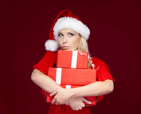 one item: Pretty girl in Christmas cap hands a set of presents, isolated on purple