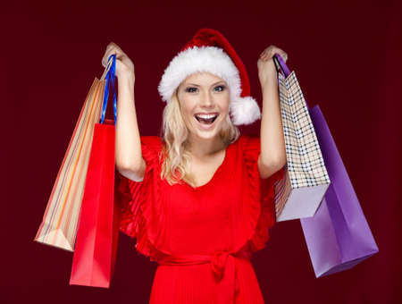 Pretty woman in Christmas cap hands shopping packets, isolated on purple photo