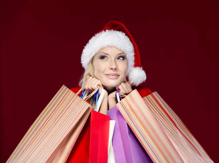 Woman in Christmas cap hands paper packets, isolated on purple photo