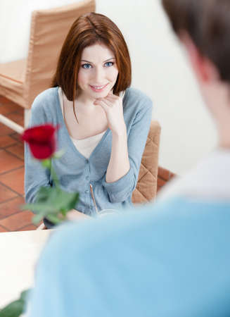 Man presents a crimson rose to his girlfriend at the cafe Stock Photo - 16041302