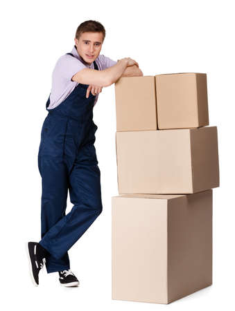 porter: Young delivery man in overalls with containers, isolated on white. Transportation service Stock Photo