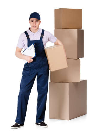 porter: Young delivery man in blue overalls and blue peaked cap hands box, isolated on white
