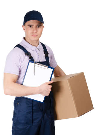 peaked: Young delivery man in blue overalls and blue peaked cap hands parcel, isolated on white