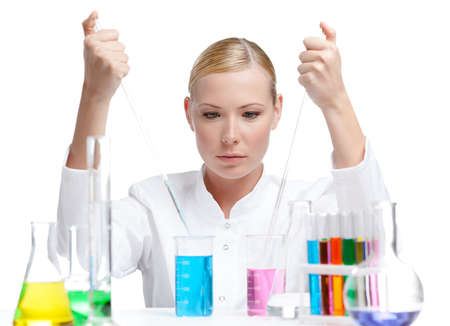 Chemical female researcher surrounded with vials and flasks makes some experiments, isolated on white Stock Photo