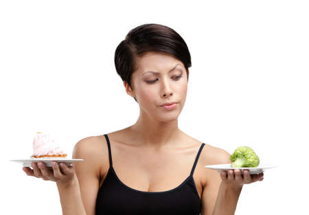 doubtfulness: Woman doubts between tasty tart and healthy vegetable, isolated on white Stock Photo