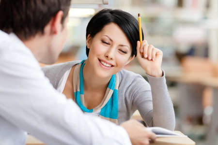 adult learning: Woman communicates with handsome man showing her something in the book at the library