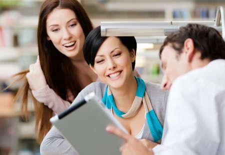 zusammenarbeit: Junger Mann sitzt am Tisch in der Bibliothek zeigt etwas Interessantes im Pad mit zwei Frauen Lizenzfreie Bilder