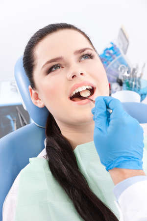 check up: Dentist is looking for the defects in the oral cavity of the patient on the dentists chair